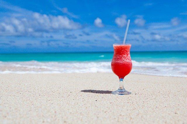 pohár s drinkom na pláži