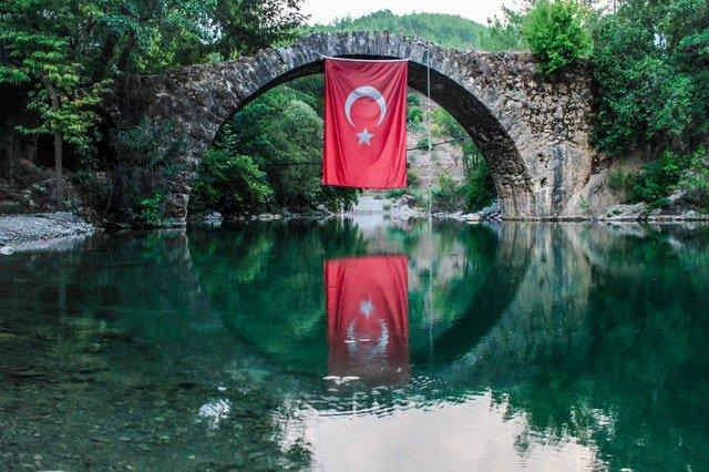 Kamenný most nad riekou, z ktorého visí turecká vlajka