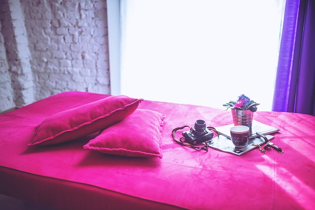 Posteľ s ružovým poťahom, na ktorej je káva, kvetináč s kvetmi a fotoaparát.jpg