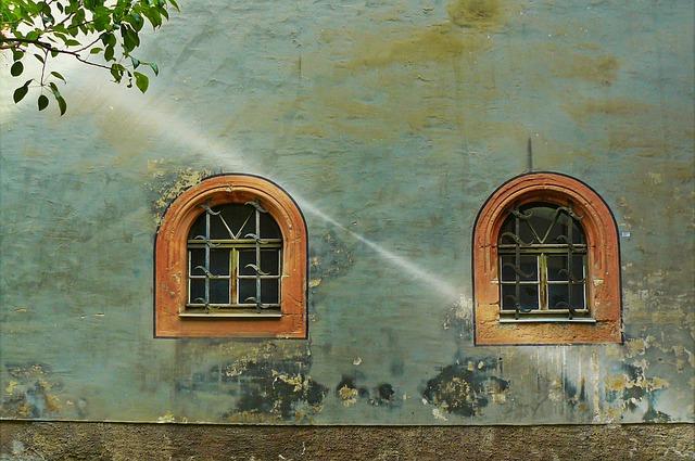 Stena domu s dvoma oknami, na ktorú dopadajú slnečné lúče