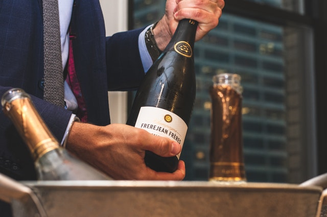 Muž v obleku drží v rukách fľašku šampanského.jpg