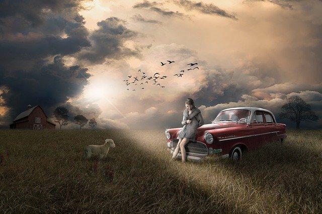 Rozprávkový obrázok červeného auta na lúke, sedí na ňom žena a vedľa ovca.jpg