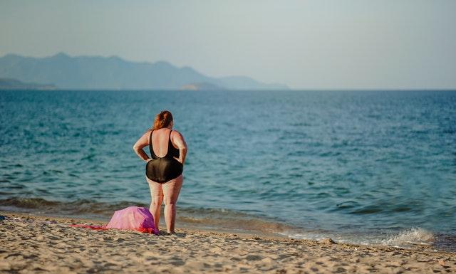 Tučná žena v čiernych plavkách stojí na pláži pri mori.jpg