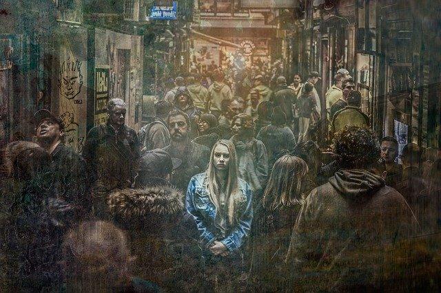 Vystresovaná žena v modrej bunde stojí uprostred hustého davu ľudí.jpg