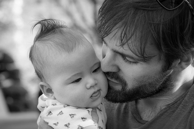 Muž drží pri svojej tvári malé bábätko.jpg