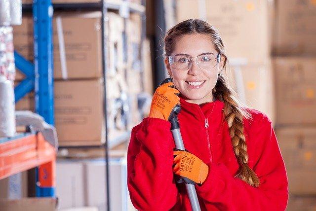 Žena v okuliaroch, červenej bunde a s rukavicami na rukách