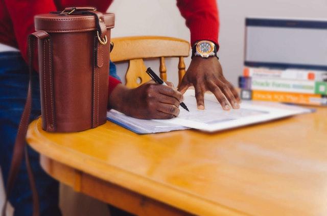 Muž v červenom svetri píše do zošita, ktorý je položený na hnedom stole