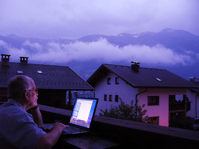 Starší muž na balkóne, notebook, večer