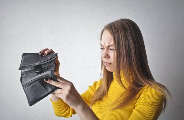 Žena v žltom svetri pozerá do čiernej peňaženky